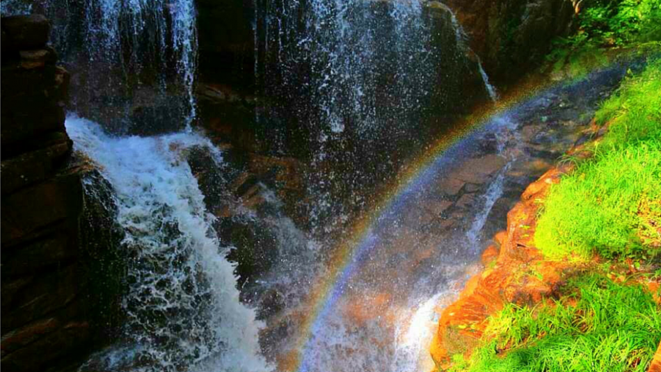 Rainbow over rocks and waterfall
